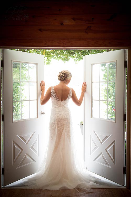 Beautiful bride poses in front of Entry doors