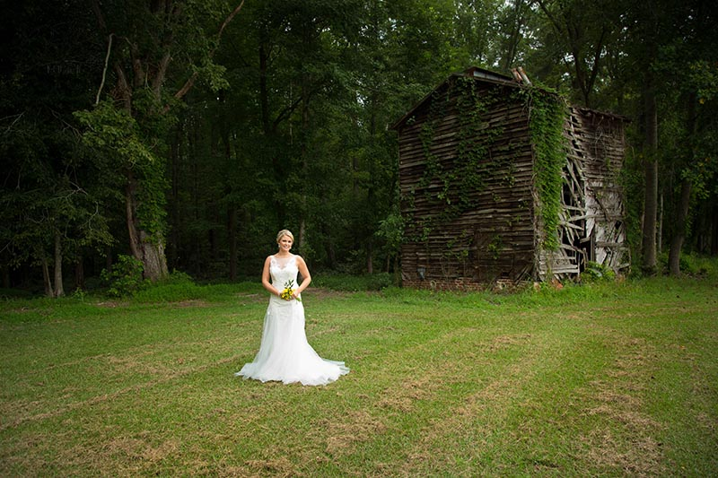 Bride Poses in front of old barn at FHF Venue